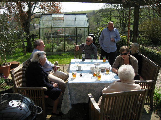friends and family gathered around table on patio