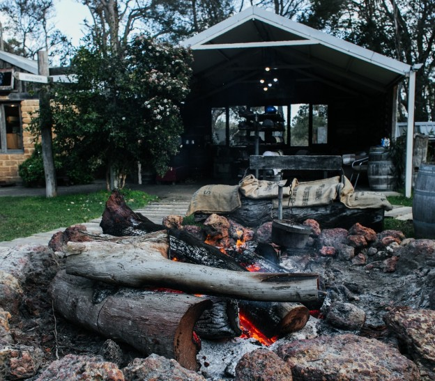 a fire pit in a backyard surrounded by big stones