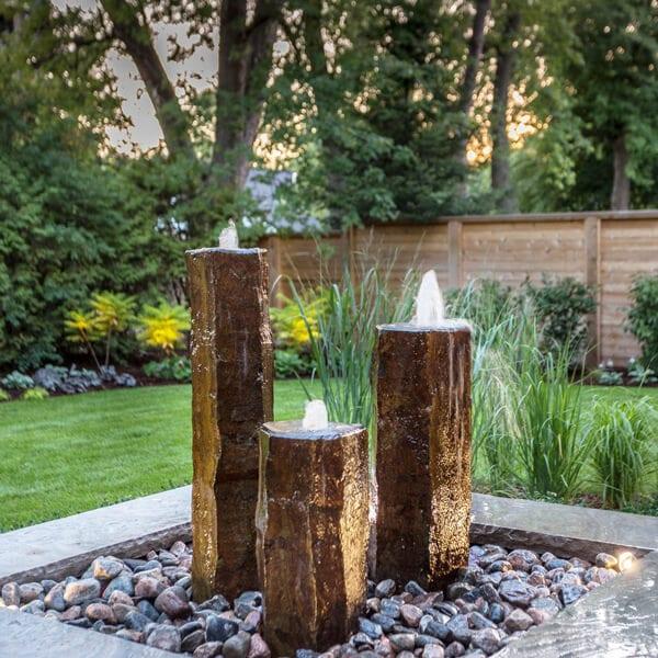 three column fountain water feature in backyard