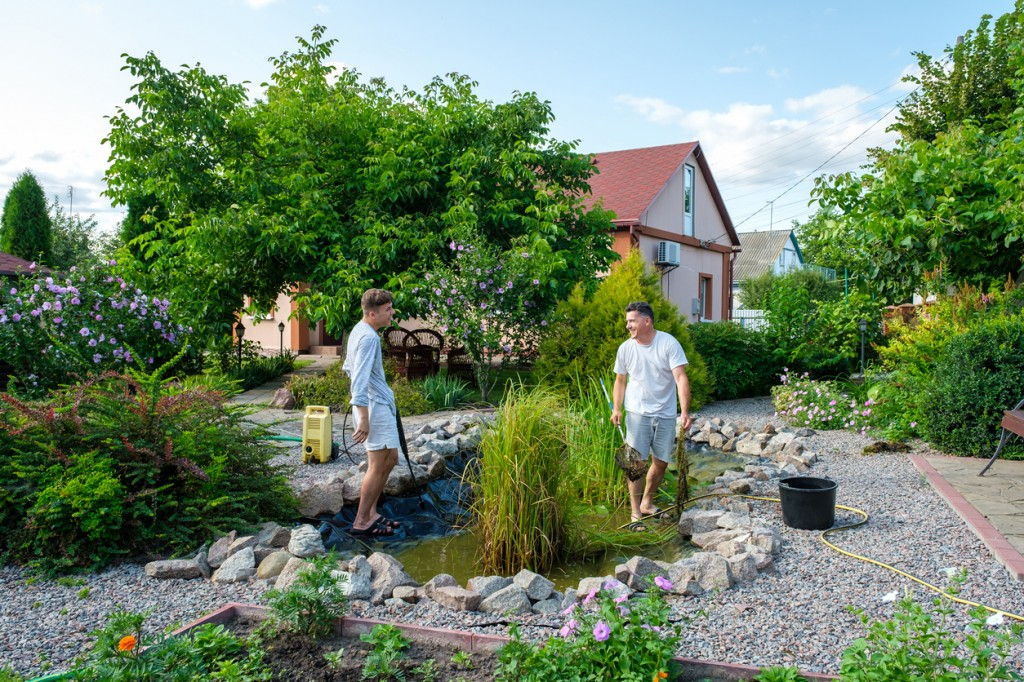 father and adult son cleaning garden pond