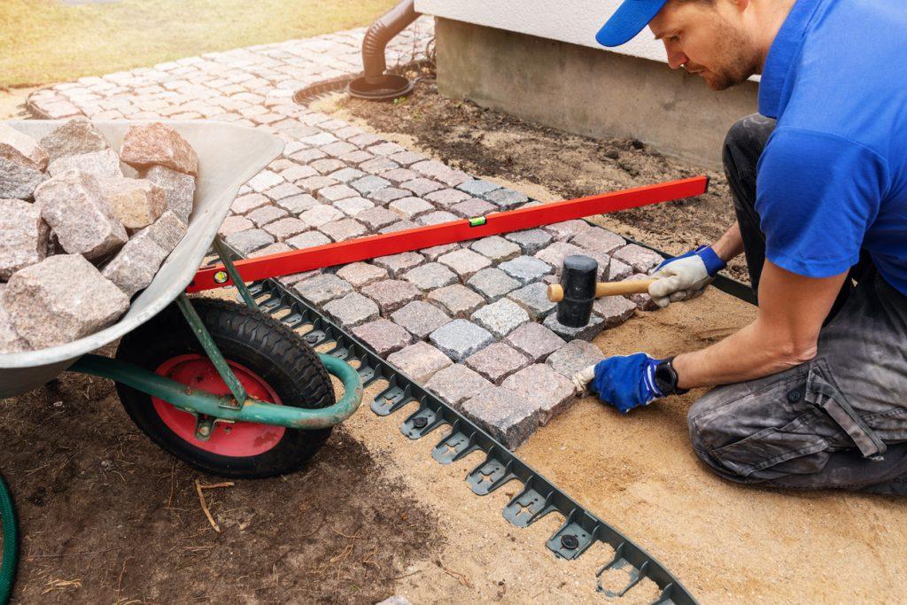 man installing walkway made of square pavers