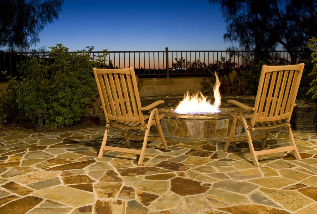 two chairs by firepit with a scenic view.  firepit and surrounding patio are constructed with pavers.