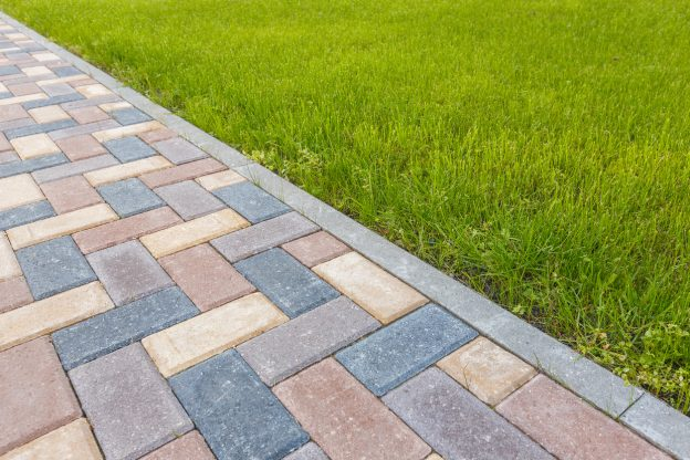 pathway of pavers bordered by lawn